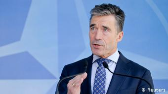Rasmussen looks off-camera in front of the NATO logo.