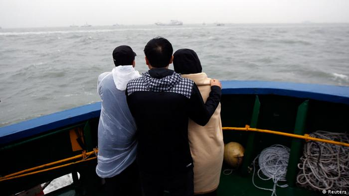 Family members of missing passengers who were on the South Korean Sewol ferry, which has sunk, look at the site of the accident in the sea off Jindo April 17, 2014. Rescuers fought rising winds and waves on Thursday as they searched for hundreds of people, mostly teenage schoolchildren, still missing after the South Korean ferry capsized more than 24 hours ago.