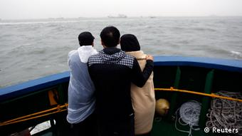 amily members of missing passengers who were on the South Korean Sewol ferry, which has sunk, look at the site of the accident in the sea off Jindo April 17, 2014.