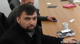 Denis Pushilin sits at a table with other individuals.