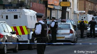 A picture showing police vans and incident tape in Northern Ireland after one of the former IRA leaders is shot