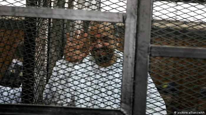 Mohammed al-Beltagy waves from behind bars during his trial in 2014.
