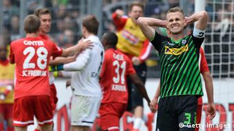Freiburg players celebrate a goal against Borussia Mönchengladbach, while Gladbach's captain Filip Daems (in the foreground) displays grasps his head in frustration.