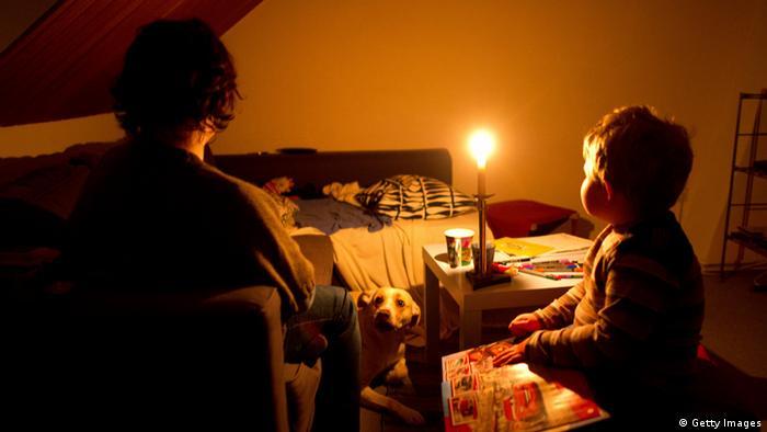 Eine Mutter sitzt mit ihrem Kind zu Hause bei Kerzenschein