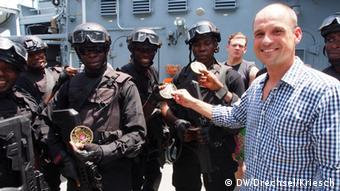 Soldiers and a man with a blue-white checkered shirt hold miltary badges men on a ship (Foto: Drechsel/Kriesch/DW)