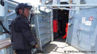 A soldier with a machine gun stands in front of a door men on a ship (Foto: Drechsel/Kriesch/DW)