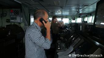 A man stands on a bridge and holds a phone handset men on a ship (Foto: Drechsel/Kriesch/DW)