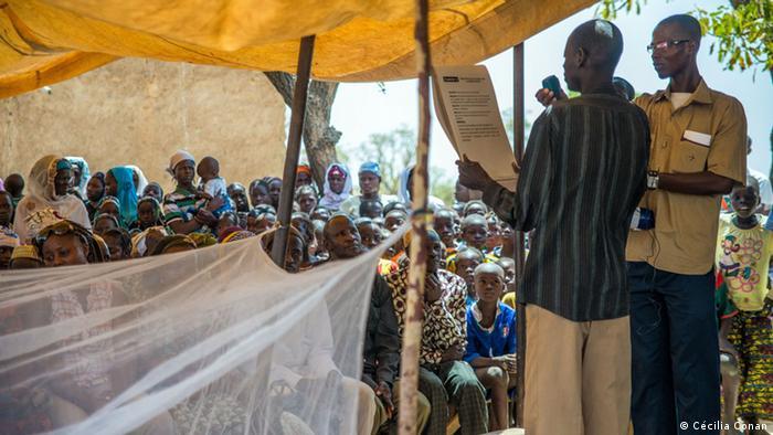 Ein Gesundheitsarbeiter erzählt bei einer Gemeindeversammlung in Burkina Faso, wie man Malariainfektionen vorbeugen kann (Foto: Cécilia Conan)