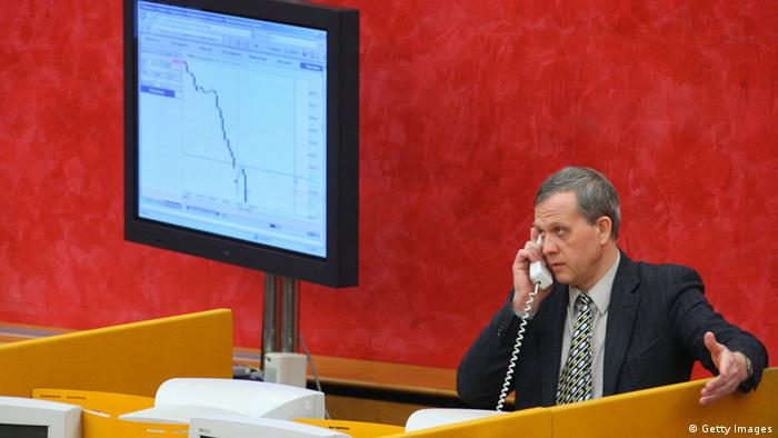 A Russian stock broker speaks on the phone inside the MICEX stock market