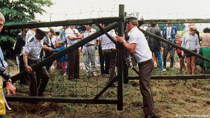 Austrian border guards opening a wooden gate in the wire border fence with Hungary as people behind it wait to cross.