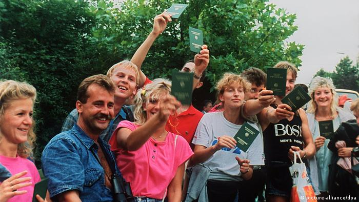 A group of happy East Germans waving their passports after crossing the Hungarian-Austrian border in August 1989.