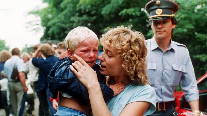 A blonde woman comforting a crying child in her arms, a policeman in the background, at the border between Hungary and Austria the day 600 East Germans made the crossing.