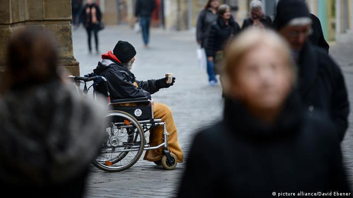 Man in wheelchair, begging in pedestrian zone