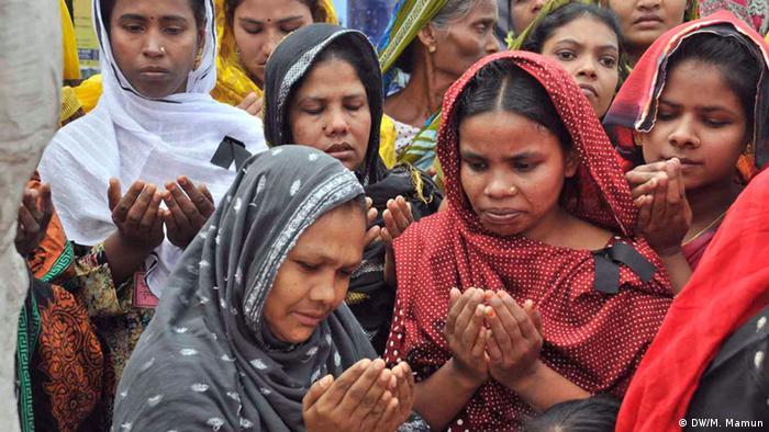 Parentes de vítimas fatais do desabamento do prédio Rana Plaza, que abrigava fábricas têxteis, rezam pelos mortos em 2014
