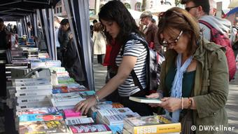 Women leafing through books at Placa de Catalunya (Photo: Hans-Günter Kellner / DW)