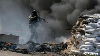 A Ukrainian security force officer is deployed at a checkpoint set on fire and left by pro-Russian separatists near Slaviansk April 24, 2014. (Photo: REUTERS/Gleb Garanich)