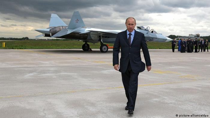 Vladimir Putin walks away from a T-50 fighter jet