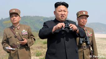Kim Jong-Un watches a military parade