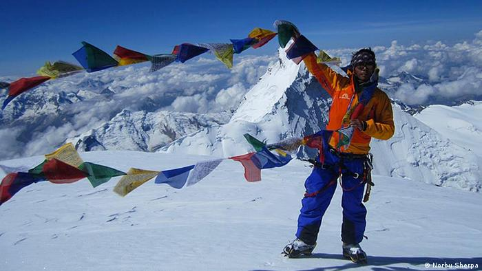 Everest climber stands at the peak with Nepalese flags