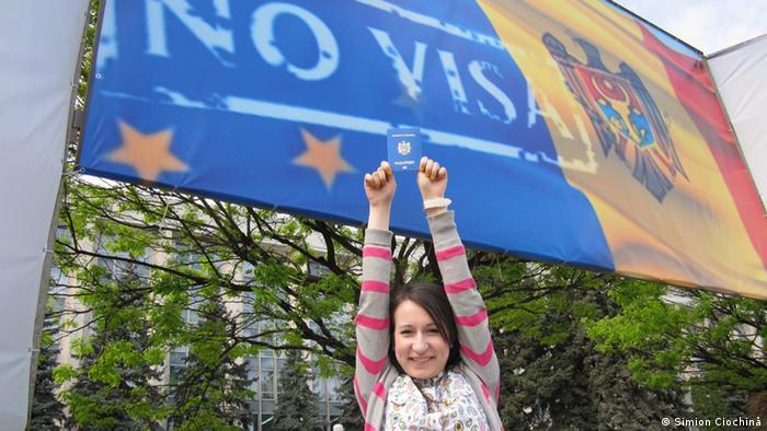 Девушка держит в вытянутых руках паспорт Молдавии на фоне плаката Виз больше не надо