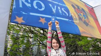 Девушка с молдавским паспортом на фоне плаката, посвященного безвизовому режиму с ЕС
