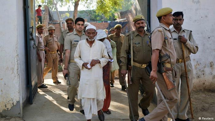 A Muslim man, who was displaced by deadly religious strife last year, arrives to cast his vote for the general election at a polling station escorted by police in Palra village, in Muzaffarnagar district in the northern Indian state of Uttar Pradesh April 10, 2014. The election is spread out over five weeks, with voting ending on May 12. It was the turn of voters in Delhi, the capital, on Thursday and many parts of Uttar Pradesh, including Muzaffarnagar, where Narendra Modi's popularity is running high and Muslims are worried about their future. For many of the 815 million registered to vote, Modi and his Bharatiya Janata Party (BJP) represent a promise of better governance, industrial growth and job creation. REUTERS/Anindito Mukherjee