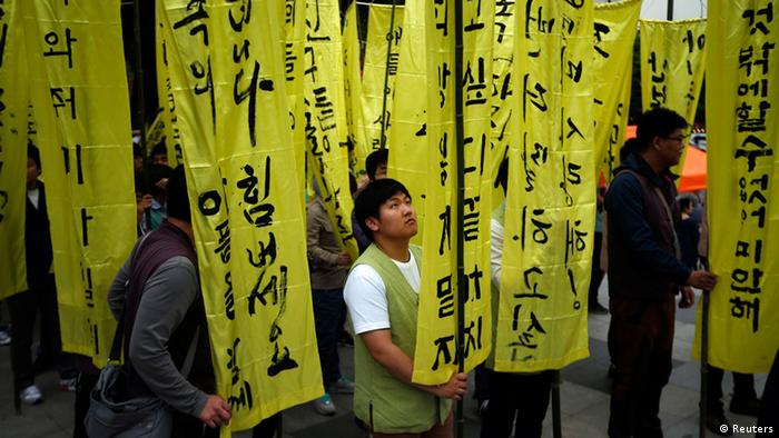 A participant looks at a funeral streamer bearing a message for victims of the capsized passenger ship Sewol, before a lotus lantern parade to celebrate the upcoming birthday of Buddha and to commemorate the victims, in Seoul April 26, 2014. The Sewol ferry sank on April 16 on a routine trip south from the port of Incheon to the traditional holiday island of Jeju.
