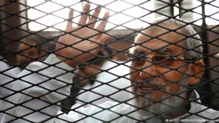 Egyptian Muslim Brotherhood's supreme guide, Mohamed Badie waves from inside the defendants cage during the trial of Brotherhood members on February 3, 2014 in the police institute near Cairo's Turah prison. The trial resumes of Mohamed Badie and more than 50 others on charges of inciting violence that left two dead in the Nile Delta city of Qaliub, after the ouster of Islamist president Mohamed Morsi. AFP PHOTO / AHMED GAMIL (Photo credit should read AHMED GAMIL/AFP/Getty Images)
