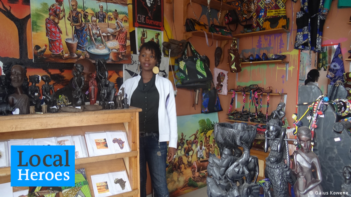 Mapendo Sumuni stands in the middle of her shop, surrounded by carvings and paintings. Photo: Gaius Kowene