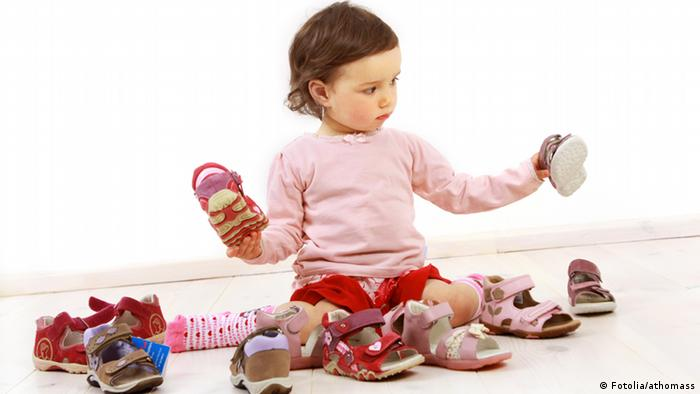 Young child holding up shoes, with lots of shoes surrounding it