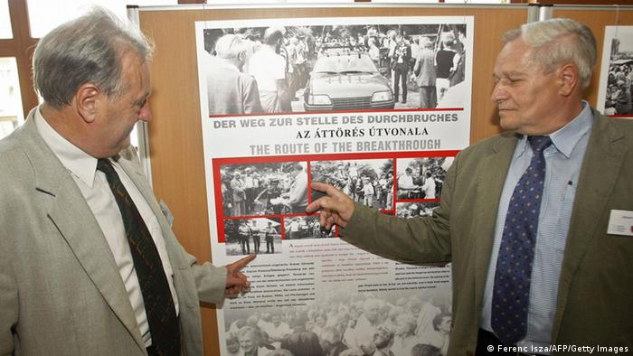 Former Hungarian border official Arpad Bella (left) with his Austrian colleague Johann Gottl in 2009, in front of a board with photos of the day of the 1989 border crossing