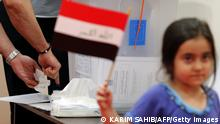 An Iraqi national residing in the UAE dips his finger in ink after casting his ballot for Iraq's parliamentary elections at a polling station in Dubai on April 27, 2014. Iraqi expats head to the polls today as in Iraq the polls will open on April 30, with little sign of any respite in the bloodshed, and the country still looking to rebuild after decades of conflict and sanctions. AFP PHOTO/KARIM SAHIB (Photo credit should read KARIM SAHIB/AFP/Getty Images)