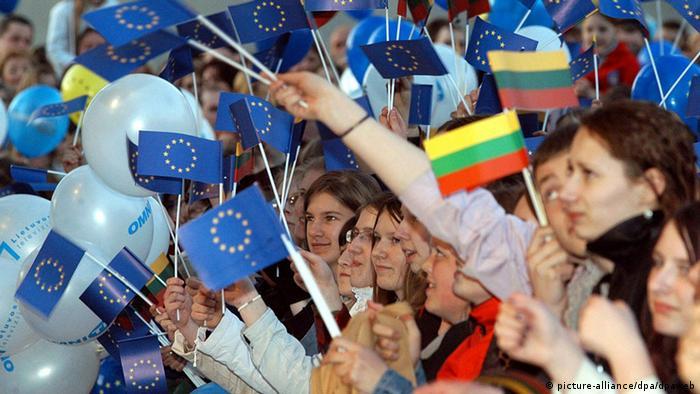 Жители Литвы с флажками своей страны и ЕС празднуют вступление в Евросоюз