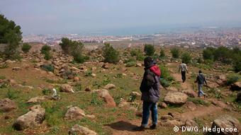 View of Melilla from the top of Mount Gourougou; some migrants walking across the scrubby ground. Photo: Guy Hedgecoe