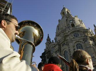 Cánticos y percusión frente a la Iglesia de Nuestra Señora de Dresde, resurgida de las cenizas.