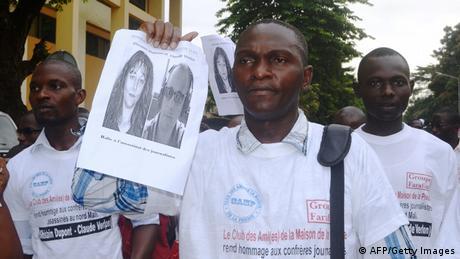 Ein Mann hält einen Ausdruck hoch, auf dem zwei französische Journalisten zu sehen sind, die im November 2013 in Mali getötet wurden. (Foto: AFP/Getty Images)