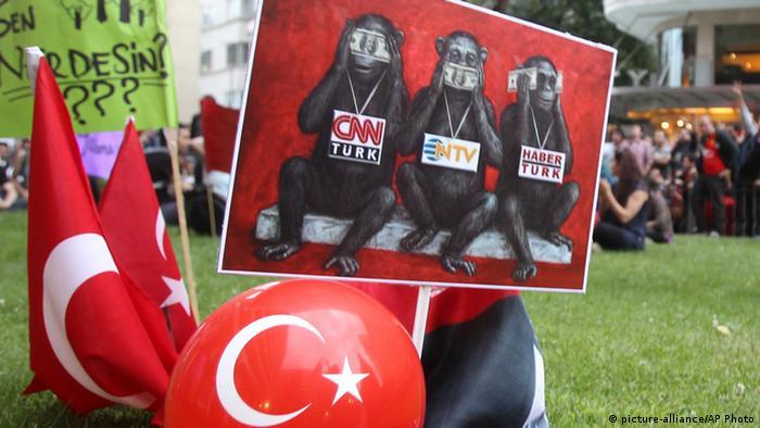 Plakat mit den drei Affen, die nichts hören, nichts sehen und nichts sagen. Sie haben Geldscheine in den Händen und Schilder umgehängt, auf denen die Namen türkischer Medien stehen. (Foto: picture-alliance/AP Photo)