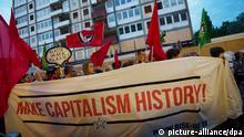 Demonstranten halten am 30.04.2014, während der Demonstration am Vorabend zum 1. Mai, in Hamburg vor den sogenannten Esso-Häusern ein Transparent mit der Aufschrift Make Capitalism History!, Foto: Maja Hitij/dpa