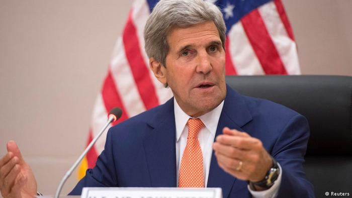 John Kerry with the US flag behind him