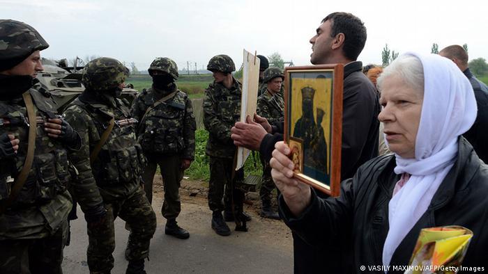 Eine Frau hält Soldaten eine Ikone entgegen (Foto: Reuters)