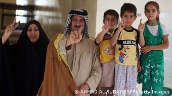 A woman in a black Burka, a man with a black-and-white chequered turban and three children show their inked forefinger (Foto: Ahmad al-Rubaye/AFP/Getty Images