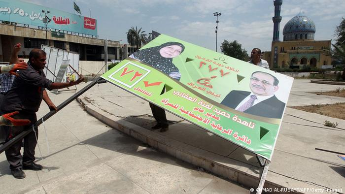 A man takes down an election poster showing al-Maliki (Foto: Ahmad al-Rubaye/AFP/Getty Images)