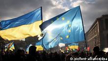 FILE - Two men hold EU and Ukrainian flags during the pro-European protests rally at Independent Square in Kiev, Ukraine, 05 December 2013. EPA/ZURAB KURTSIKIDZE (zu dpa «Europa sucht bei Krisen-Gipfel gemeinsamen Kurs gegenüber Moskau» vom 18.03.2014) +++(c) dpa - Bildfunk+++