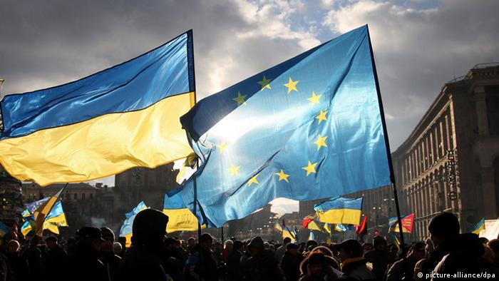 Two men hold EU and Ukrainian flags during the pro-European protests rally (photo: EPA/ZURAB KURTSIKIDZE)