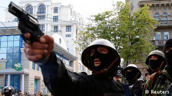 Одетый в маску и каску молодой человек держит пистолет во время столкновений 2 мая в Одессе