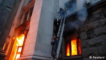 People wait to be rescued on the second storey's ledge during a fire at the trade union building in Odessa May 2, 2014. At least 38 people were killed in a fire on Friday in the trade union building in the centre of Ukraine's southern port city of Odessa, regional police said. (Photo via REUTERS/Yevgeny Volokin)