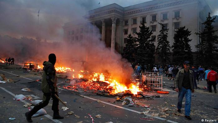 A protester walks past a burning pro-Russian tent camp near the trade union building in Odessa May 2, 2014. (Photo via REUTERS/Yevgeny Volokin)