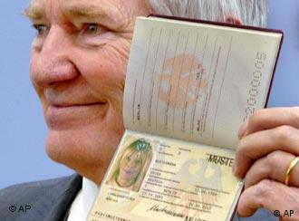Otto Schily showing off a biometric passport -- clearly not his own