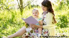 happy mother reading a book to baby outdoors 64054575