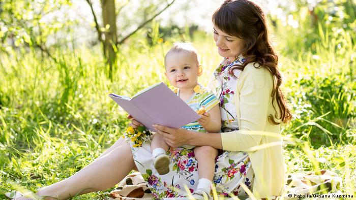 Symbolbild Mutter mit Baby Buch lesen vorlesen Natur